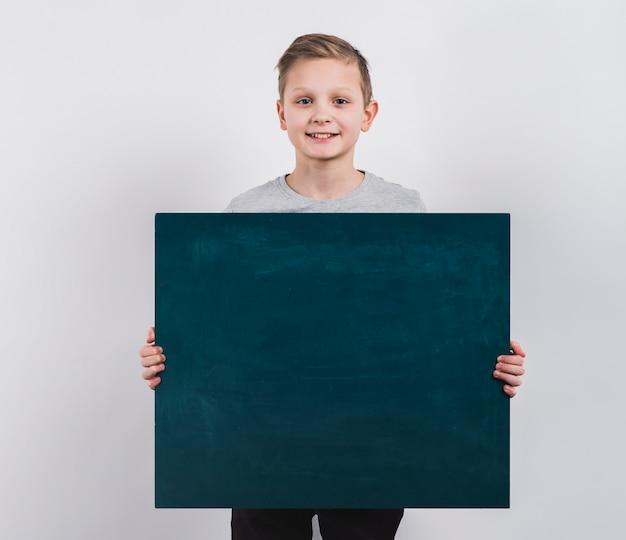 Retrato de un muchacho sonriente que sostiene la pizarra en blanco contra fondo gris