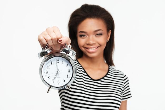 Retrato de una mujer adolescente africana feliz mostrando despertador