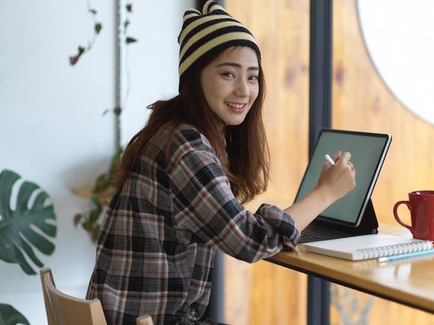 Retrato de mujer adolescente haciendo los deberes con tableta digital en mesa de madera