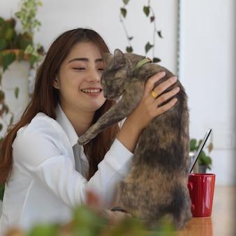 Retrato de mujer adolescente jugando con su gato mientras se relaja con tableta digital en la sala de estar