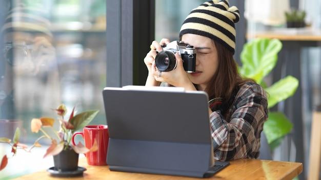 Retrato de mujer adolescente tomando fotos con cámara digital mientras está relajado sentado en el café