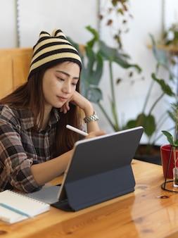 Retrato de mujer adolescente trabajando con tableta digital en mesa de madera con taza de café y jarrón de plantas