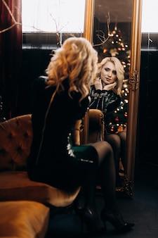 Retrato de una mujer adorable en vestido negro posando en un acogedor cuarto oscuro con decoración de navidad