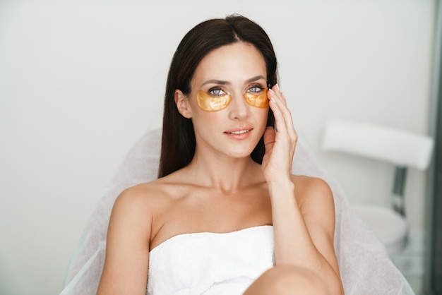 Retrato de mujer adulta caucásica con parches en los ojos mientras está sentado en un salón de belleza