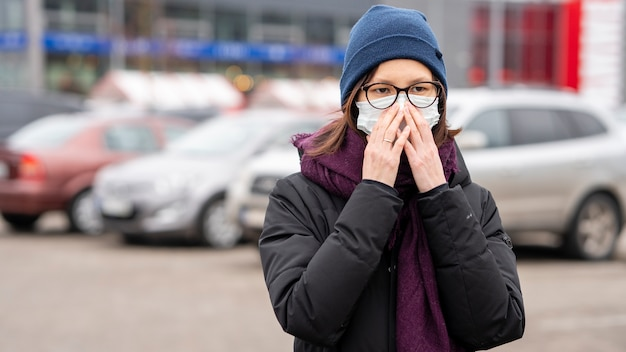 Retrato de mujer adulta con máscara quirúrgica al aire libre