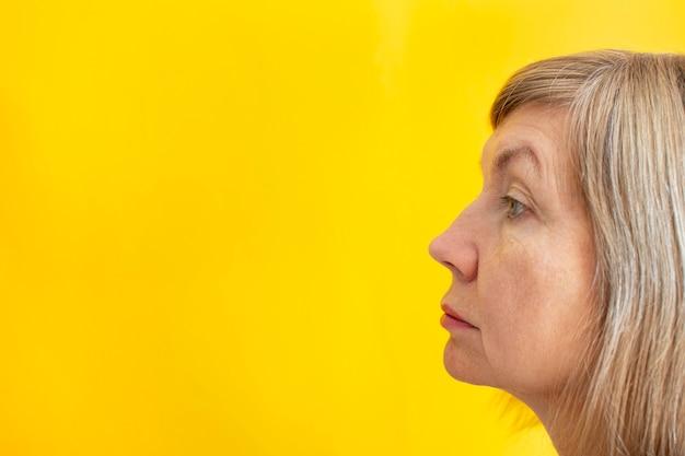 Retrato de una mujer adulta, de pie de perfil. aspecto natural. sobre un fondo amarillo. lugar para su texto. copia espacio