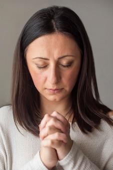 Retrato de mujer adulta rezando en casa