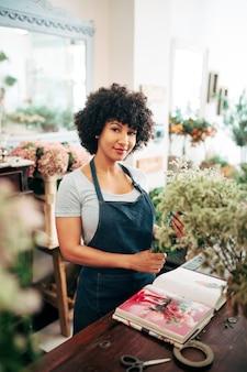Retrato de una mujer africana con álbum de fotos de flores en el escritorio en la tienda