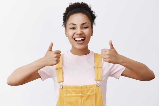 Retrato de mujer africana atractiva en monos amarillos de moda, mostrando los pulgares para arriba