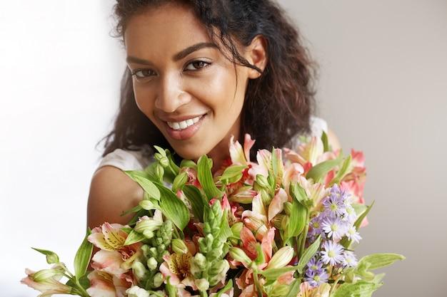 Retrato de la mujer africana hermosa que sonríe sosteniendo el ramo de alstroemerias.