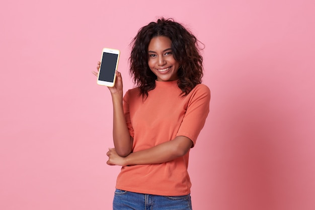 Retrato de la mujer africana joven feliz que muestra en el teléfono móvil de la pantalla en blanco aislado sobre rosa.