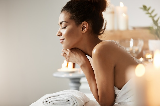 Retrato de mujer africana satisfecha relajante con los ojos cerrados en el salón de spa.