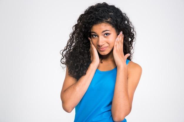 Retrato de una mujer africana tapándose los oídos aislado en una pared blanca