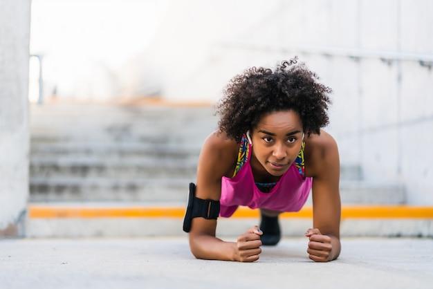 Retrato de mujer afro atleta haciendo flexiones en el piso al aire libre. concepto de deporte y estilo de vida saludable.