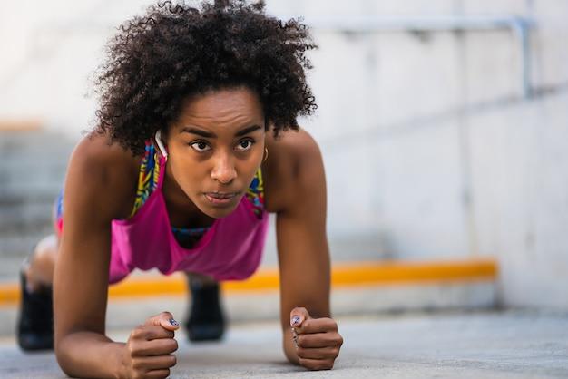 Retrato de mujer afro atleta haciendo tablones en el piso al aire libre