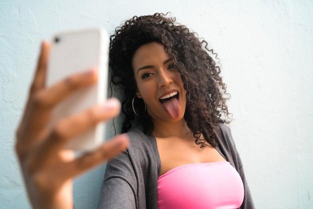 Retrato de mujer afro tomando selfies con su teléfono mophile contra la pared gris. concepto de tecnología.
