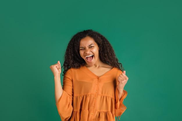 Retrato de mujer afroamericana aislado en verde con copyspace