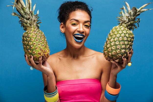 Retrato de mujer afroamericana alegre con maquillaje de moda sonriendo y sosteniendo dos piñas en ambas manos aisladas, sobre pared azul