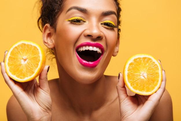 Retrato de mujer afroamericana atractiva con maquillaje de moda sosteniendo dos mitades de naranja en ambas manos aisladas, sobre pared amarilla