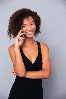 Retrato de una mujer afroamericana feliz hablando por teléfono sobre pared gris