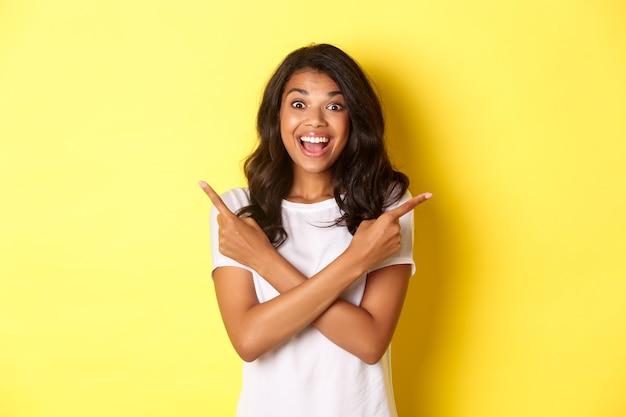 Retrato de mujer afroamericana feliz y sorprendida que muestra dos ofertas promocionales señalando con el dedo