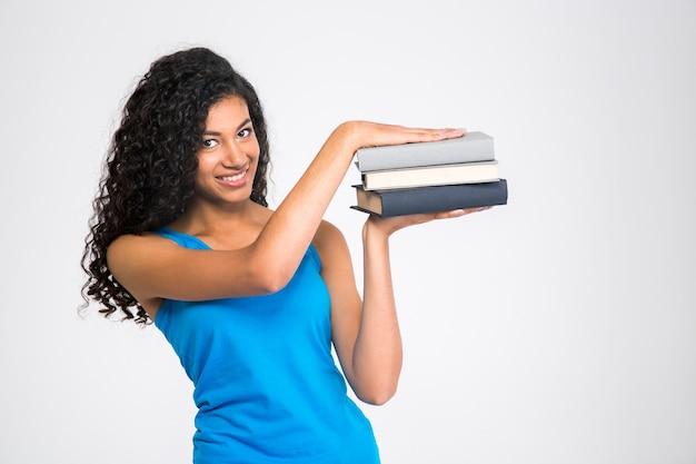 Retrato de una mujer afroamericana feliz sosteniendo libros aislado en una pared blanca