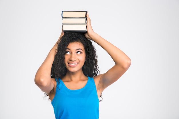 Retrato de una mujer afroamericana feliz sosteniendo libros en la cabeza aislada en una pared blanca