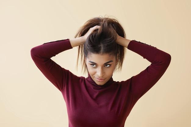 Retrato de mujer afroamericana joven elegante en suéter de cuello alto de moda mirando a otro lado con una sonrisa misteriosa como si tuviera una gran idea mientras se peina, preparándose para el trabajo por la mañana