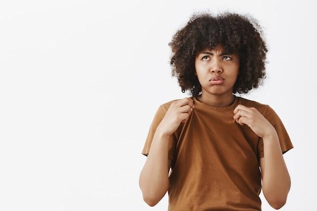 Retrato de mujer afroamericana linda triste y molesta disgustada en camiseta marrón respirando y mirando hacia el sol con disgusto por el clima