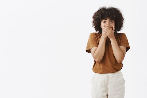 Retrato de mujer afroamericana sin palabras conmocionada presenciando una escena impactante cubriendo la boca con ambas manos de pie en estupor y mirando atónito y tembloroso