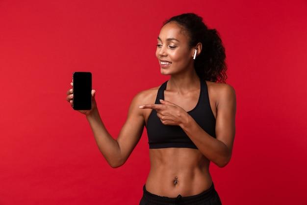 Retrato de mujer afroamericana saludable en ropa deportiva negra con smartphone y auriculares, aislado sobre pared roja