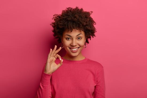 Retrato de mujer afroamericana satisfecha muestra buen gesto, dice excelente, anuncia buenas noticias, le gusta el producto y garantiza la mejor calidad, sonríe positivamente, da consejos y le gusta la elección