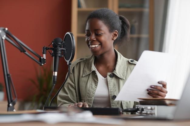 Retrato de mujer afroamericana sonriente cantando al micrófono mientras graba música en el estudio en casa, espacio de copia
