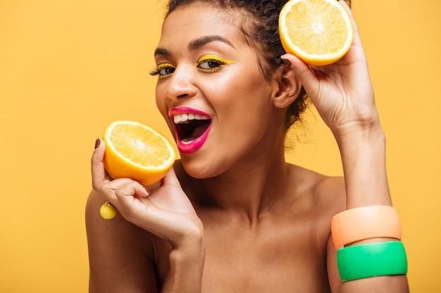 Retrato de mujer afroamericana sonriente con elegante maquillaje degustación jugosa naranja madura sosteniendo partes en ambas manos cerca de la cara aislada, sobre pared amarilla
