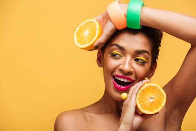 Retrato de mujer afroamericana sonriente con maquillaje elegante sosteniendo dos mitades de naranja jugosa en ambas manos aisladas, sobre pared amarilla