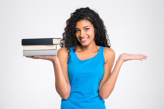 Retrato de una mujer afroamericana sonriente sosteniendo libros y copyspace en las palmas aislado en una pared blanca