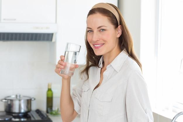 Retrato de una mujer de agua potable en la cocina