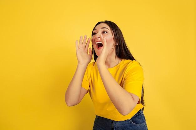 Retrato de mujer aislado en la pared amarilla del estudio
