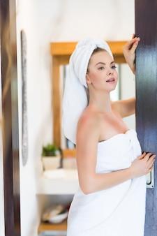 Retrato de mujer con albornoz y toalla en la cabeza de pie adentro en el baño.