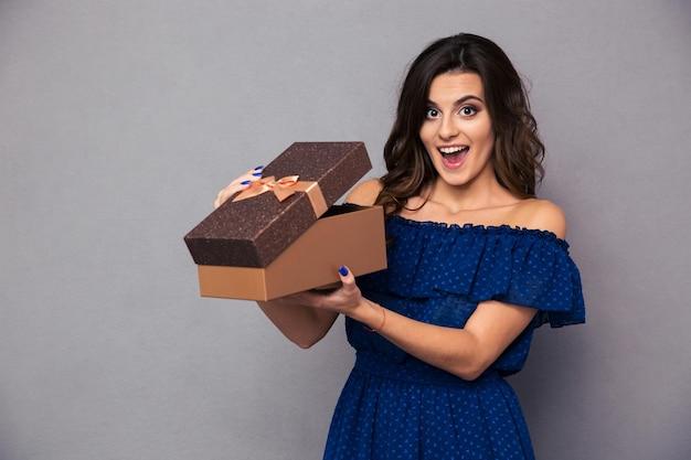 Retrato de una mujer alegre abriendo caja de regalo sobre pared gris