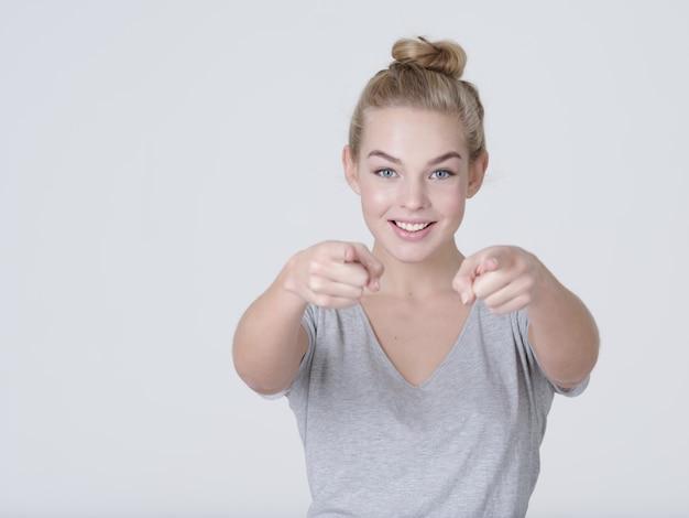 Retrato de una mujer alegre apunta a alguien - sobre fondo blanco.
