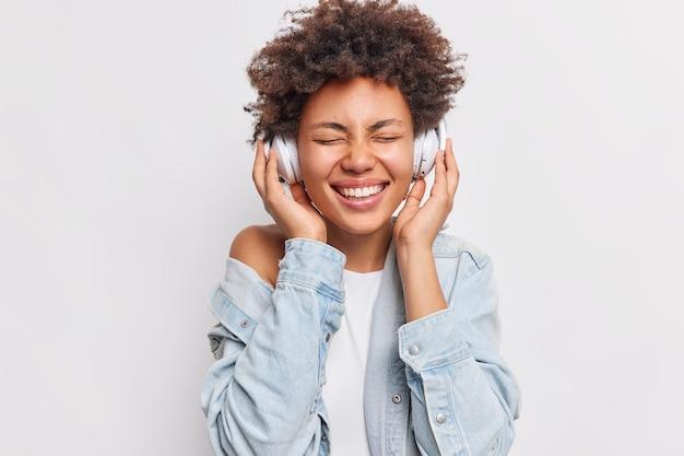 Retrato de mujer alegre con cabello afro mantiene las manos en los auriculares estéreo mantiene los ojos cerrados sonríe ampliamente muestra dientes blancos disfruta de una música agradable aislada sobre una pared blanca