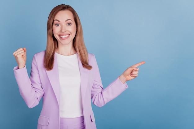 Retrato de mujer alegre elegante señalando el concepto de ganador de puño de levantar el espacio vacío