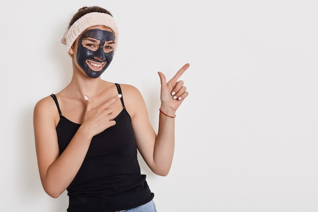 El retrato de una mujer alegre y feliz mejora la piel de su rostro, aplica una máscara exfoliante, está de buen humor, presenta modelos contra la pared blanca y señala con ambas manos a un lado.