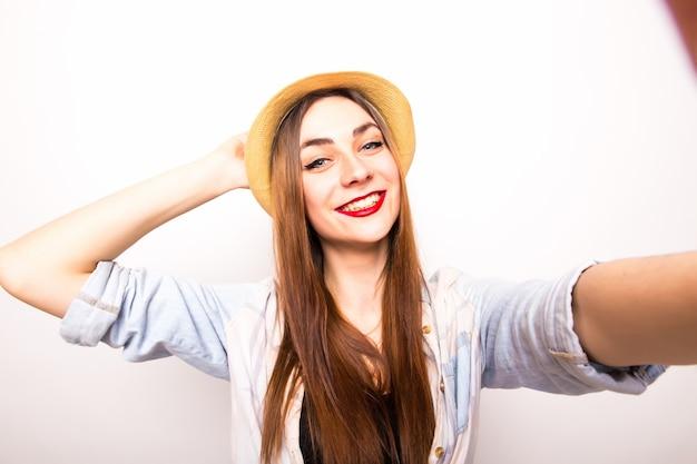 Retrato de una mujer alegre haciendo foto selfie sobre gris