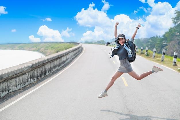 Retrato de mujer alegre y hermosa saltando mientras viaja en vacaciones