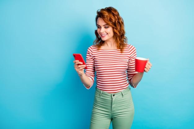 Retrato de mujer alegre positiva blogger usa su teléfono celular para comunicarse con los amigos en las redes sociales sostenga la taza con capuchino use pantalones blancos verdes pantalones aislados sobre color azul
