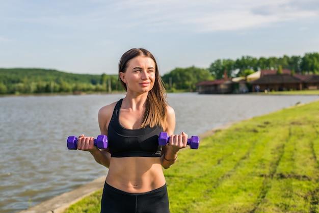 Retrato de mujer alegre en ropa deportiva haciendo ejercicio con mancuernas, al aire libre, con copyspace