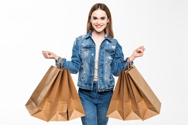 Retrato de una mujer alegre sosteniendo bolsas de compras aisladas sobre pared gris