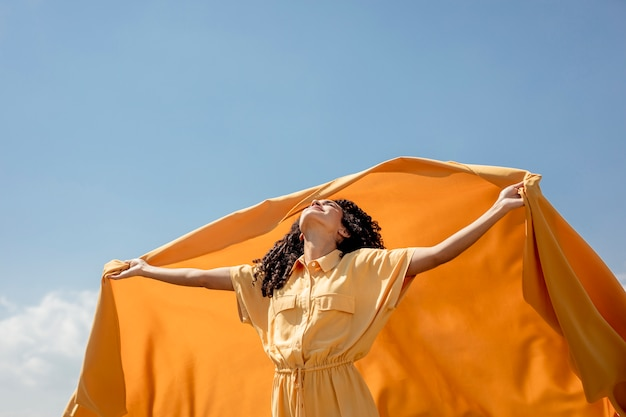 Retrato de mujer alegre con tela amarilla en la naturaleza